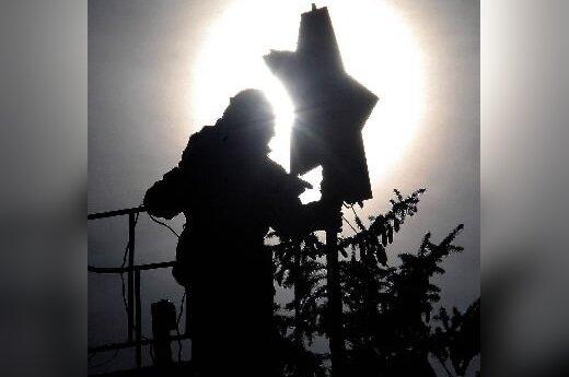 Stavropolio centre žmogus ant Kalėdinės eglės viršūnės kabina žvaigždę. Rusija.