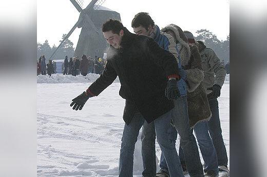 Žmonės varžosi slidinėjimo rungtyje