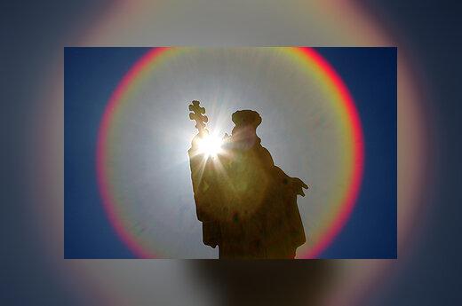 Šv.Petro aikštėje Vatikane saulės aureole apgaubta statula.