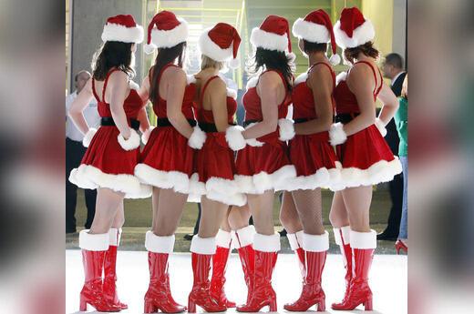 Merginos, apsirengusios Kalėdų senio kostiumais