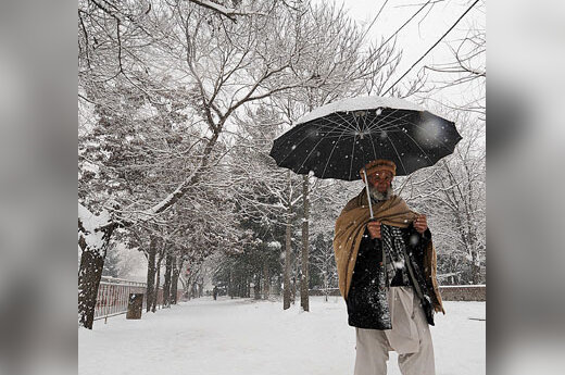 Pagyvenęs afganas žingsniuoja apsnigto Kabulo gatve