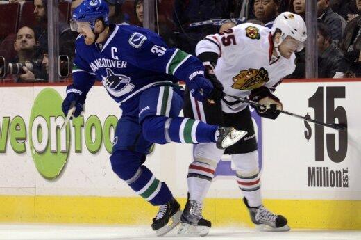"""Henrikas Sedinas (""""Canucks"""", kairėje) kovoja su Viktoru Stalbergu (""""Blackhawks"""")"""