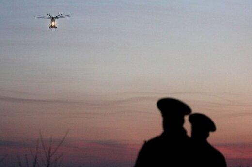 Rusijos kariškiai stebi sraigtasparnį, gabenantį žuvusiuosius prie Smolensko