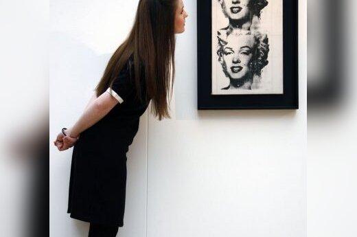 """Mergina apžiūrinėja A.Warholo paveikslą """"Dviguba Marilyn"""", eksponuojamą Londono Christie galerijoje"""