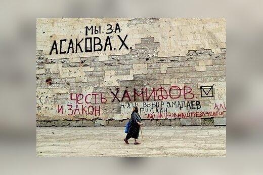 Pagyvenusi moteris Čečėnijos sostinėje Grozne eina greta sienos, kuri nurašinėta kandidatų į prezidentus pavardėmis. Sekmadienį Čečėnijoje bus renkamas naujas prezidentas.