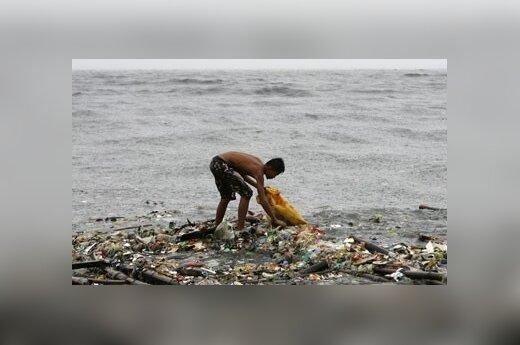 Berniukas renka vandens išplautas šiukšles