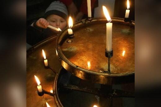 Mergytė Miuncheno bažnyčioje bando uždegti žvakelę už sunkiai sergantį Popiežių Joną Paulių II-ąjį