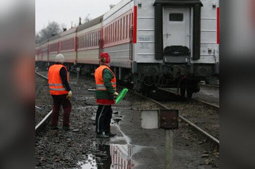 Moterys laukia, kol pravažiuos traukinys