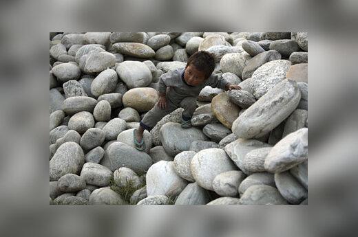 Berniukas žaidžia tarp akmenų.