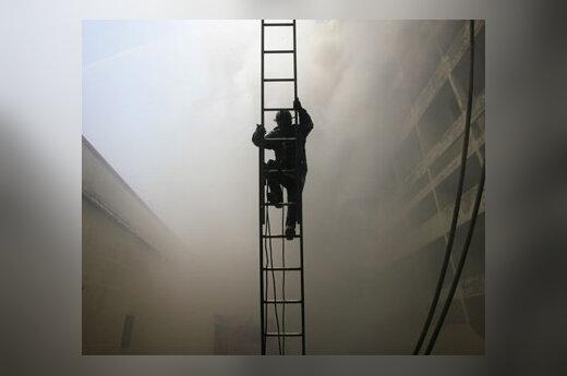 Gaisrininkas lipa kopėčiomis