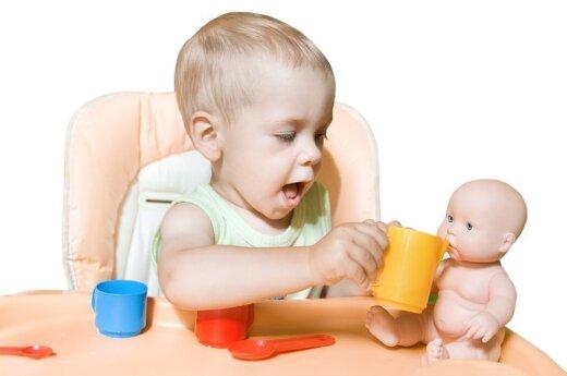berniukas žaidžia su lėle, berniukas maitina lėlę