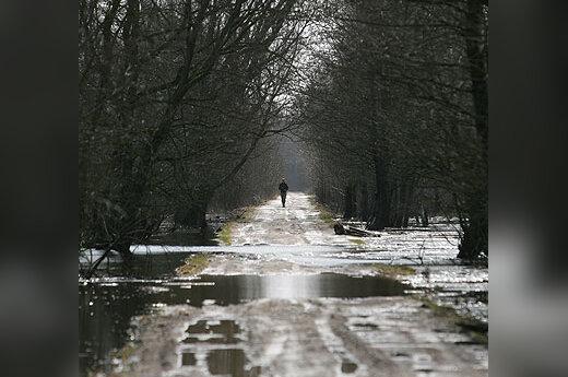 Šilutės rajono gyventojas, grįžtantis namo potvynio apsemtu keliu