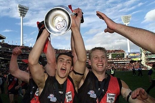 19-year-old Adam Ramanauskas celebrates the 2000 AFL Premiership with Mark Johnson.