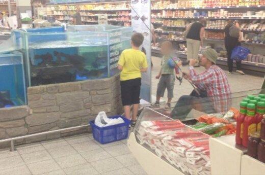 Łapał rybę w akwarium w supermarkecie